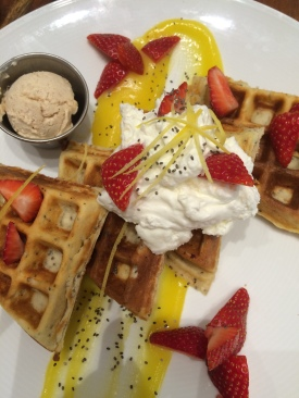 Lemon chia waffle with citrus curd, strawberries, chia seeds and vanilla whipped cream