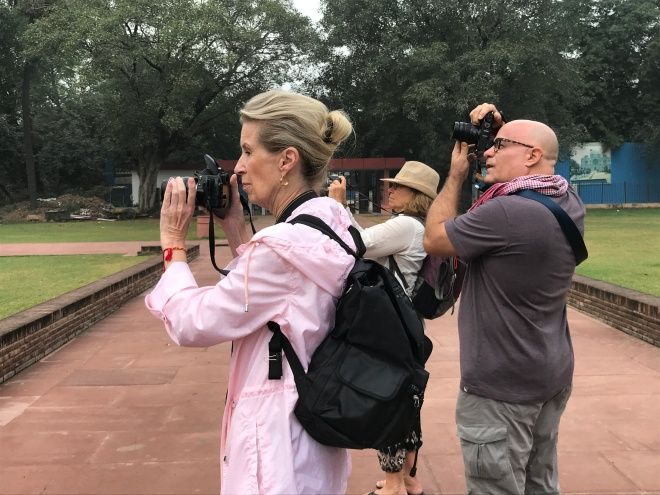 Side view of three American travelers, two women and a man, are facing left. All have cameras to their faces. The blonde woman in front is wearing a pink jacket and black backpack.
