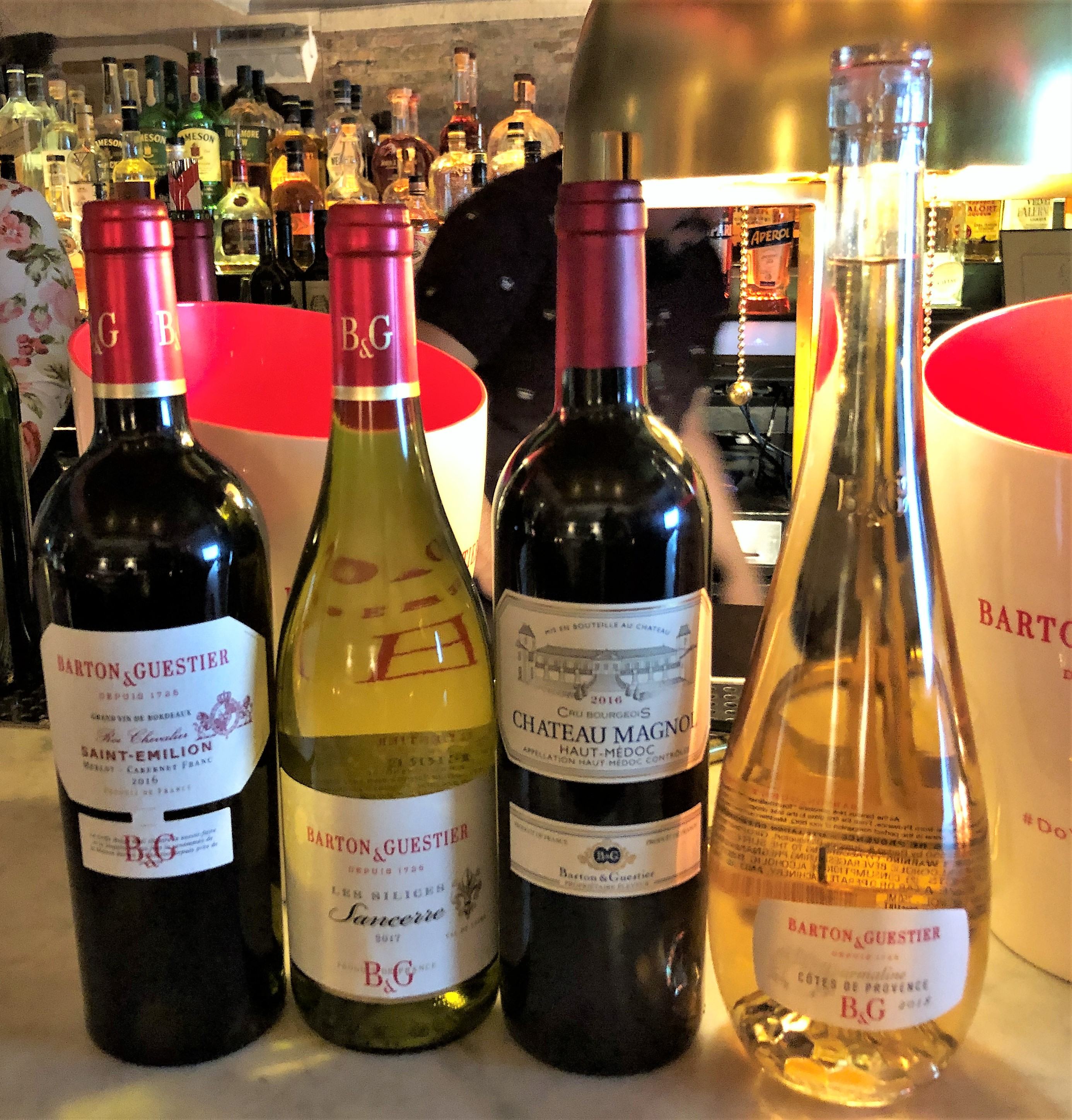 Four bottles of wine on a counter: red, white, red, white.